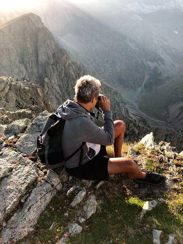 Chico con prismáticos observando montañas